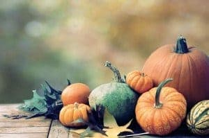 An arrangement of pumpkins and fall leaves.
