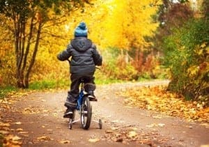 Boy riding bicycle in the fall.