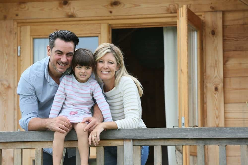Happy family on the porch of one of the Smoky Mountain log cabins in Tennessee.