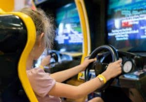 girl playing racing game in arcade